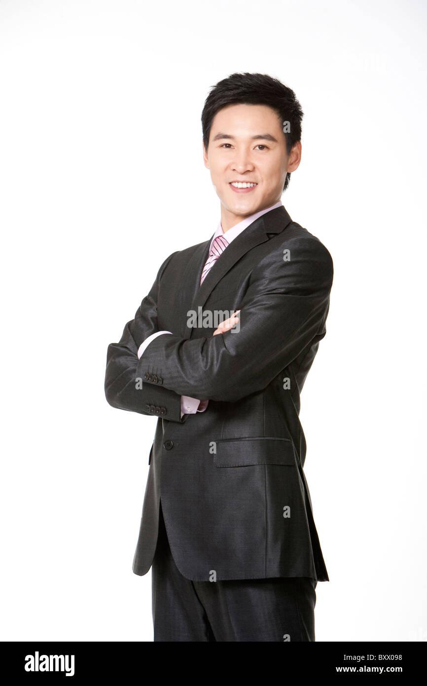 Drei Viertel Länge Geschäftsmann lächelnd mit verschränkten Armen Stockbild