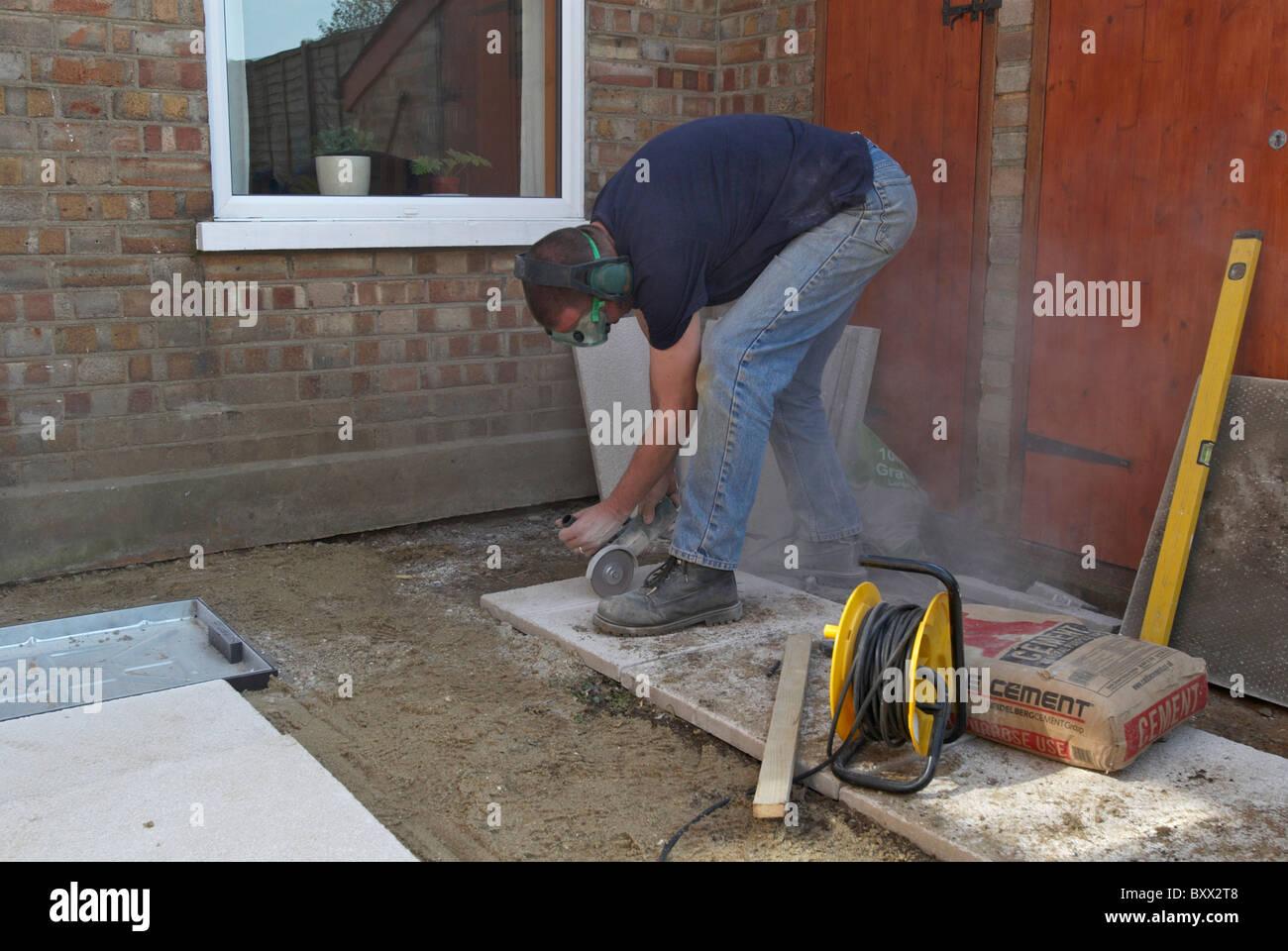 mann schneiden pflastersteine mit cutter stockfoto, bild: 33764424