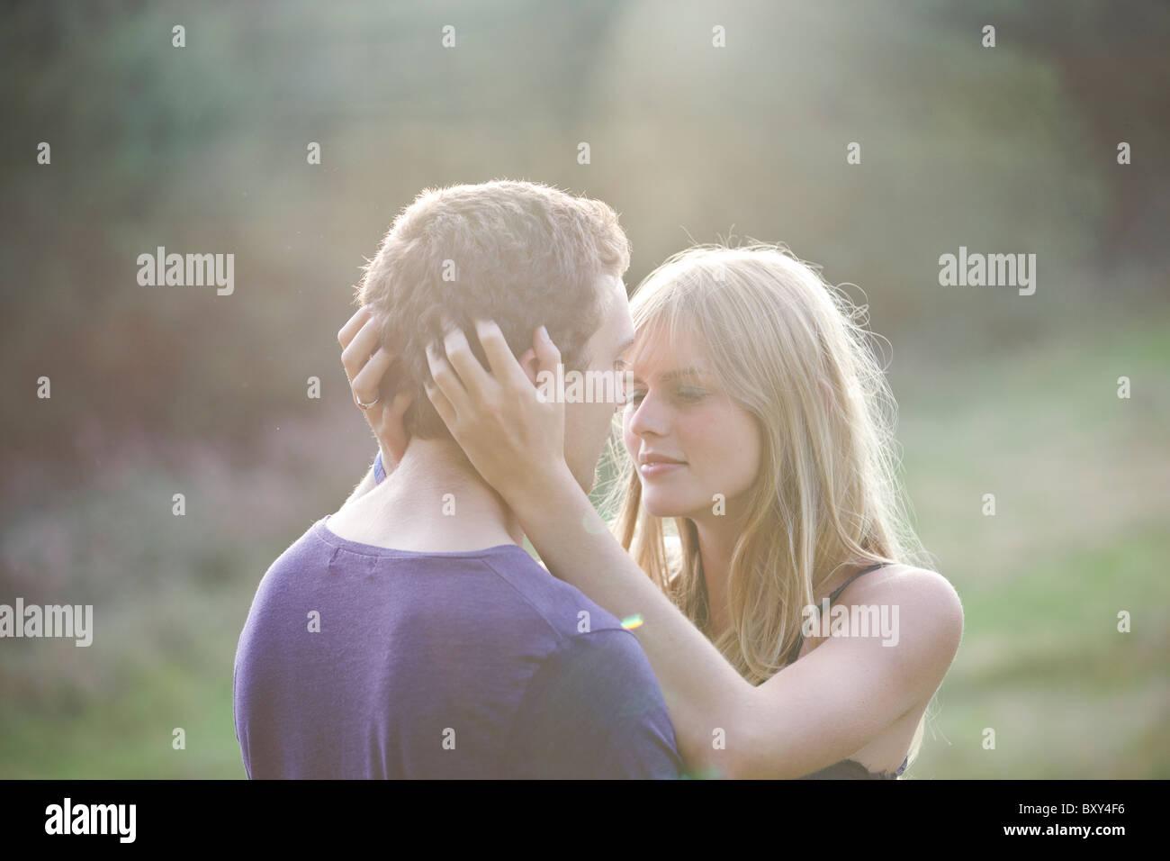 Ein romantisches junges Paar umarmen in der Abendsonne Stockbild