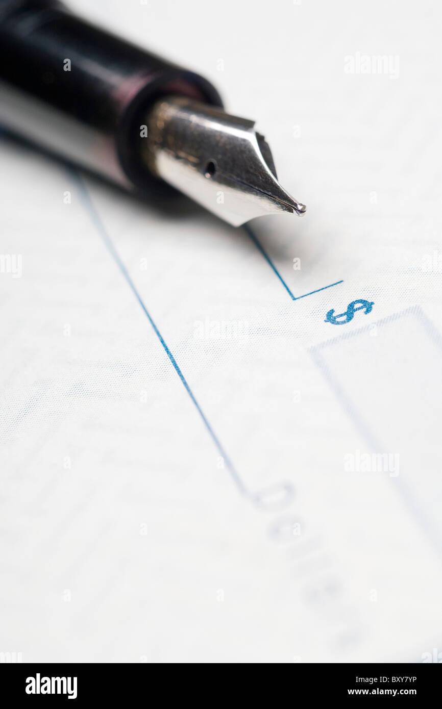 Füllfederhalter auf einen Blanko-Scheck Stockbild