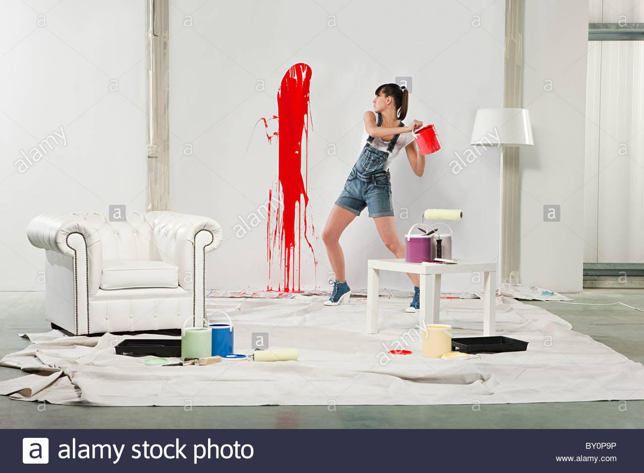 Junge Frau Spritzer roten Farbe auf weiße Wand Stockbild
