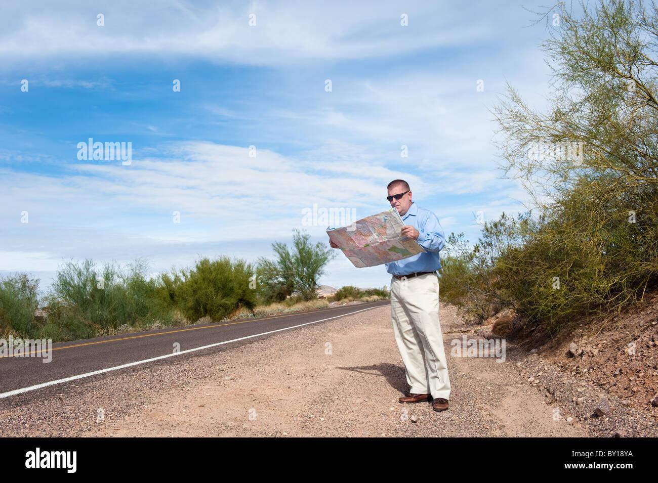 Ein verlorene Mann steht alleine auf einer einsamen Straße Kartenlesen. Stockbild