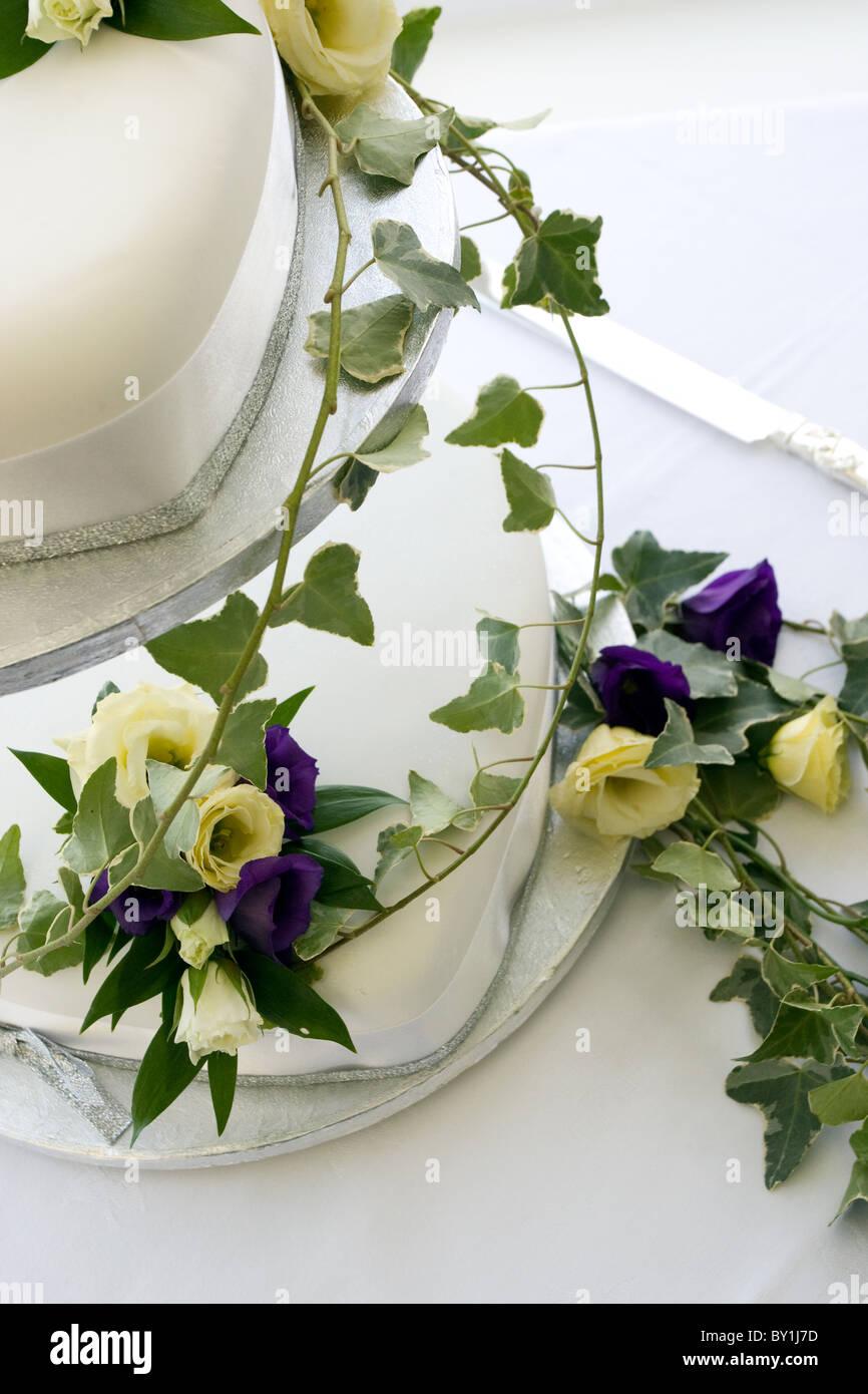 Zweistufigen weiße Hochzeitstorte drapiert in lila und Creme Blüten mit Efeu Stockbild