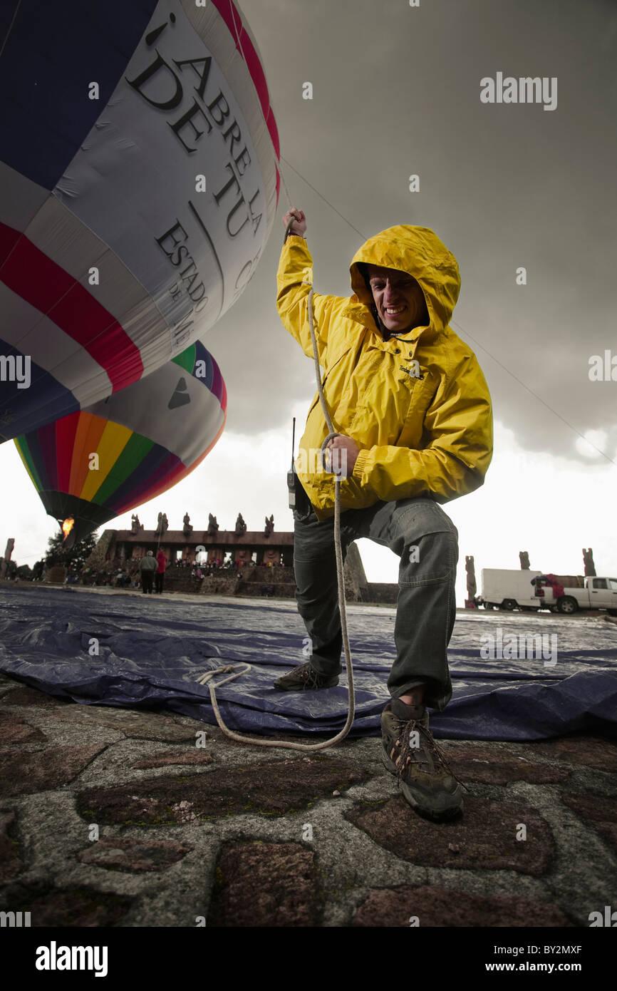 ein Mann zieht einen Ballon, während es, im Centro Ceremonial Otomi, Estado de México, Mexiko aufgeblasen Stockbild