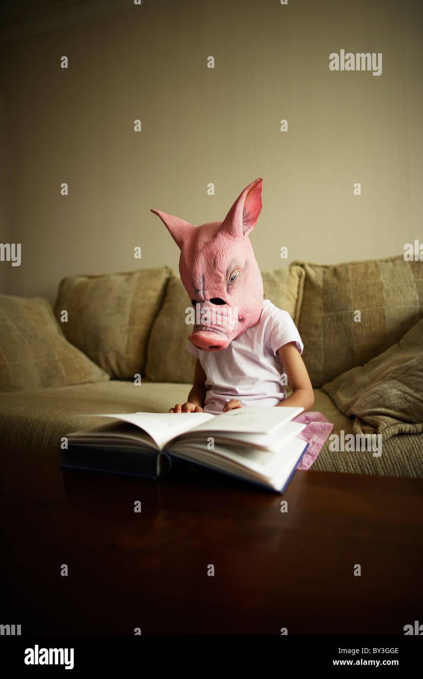Mädchen in Schwein Maske liest Buch Stockbild