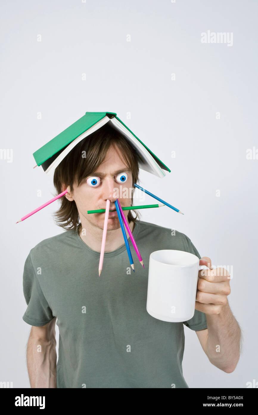 Bizarre Mann mit Bleistiften, Buch und Kaffee Stockbild