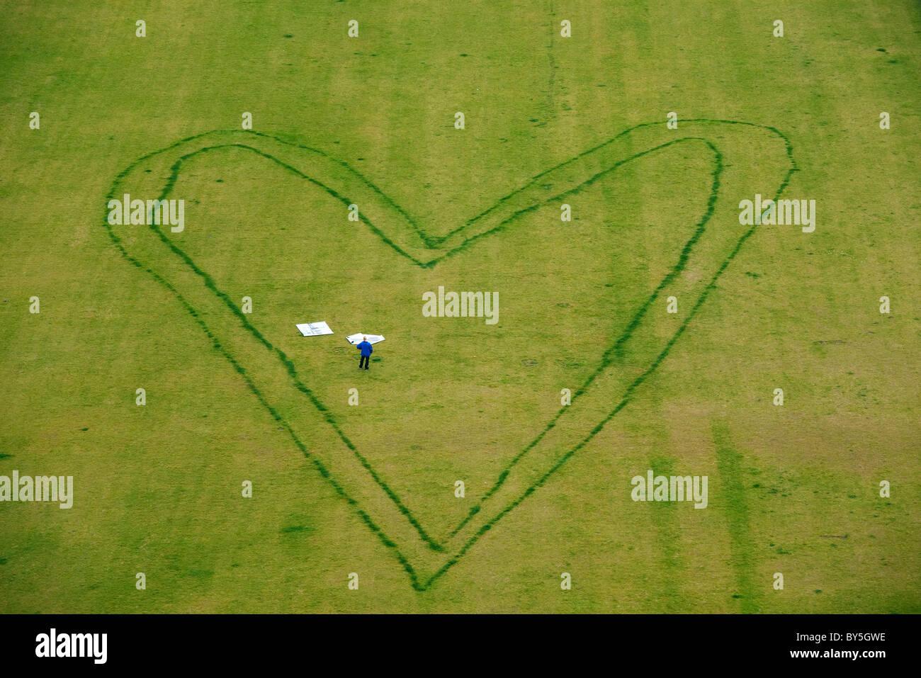 Deutschland, Berlin, riesige Herzdesign auf Rasen mit einer Person in Stockbild