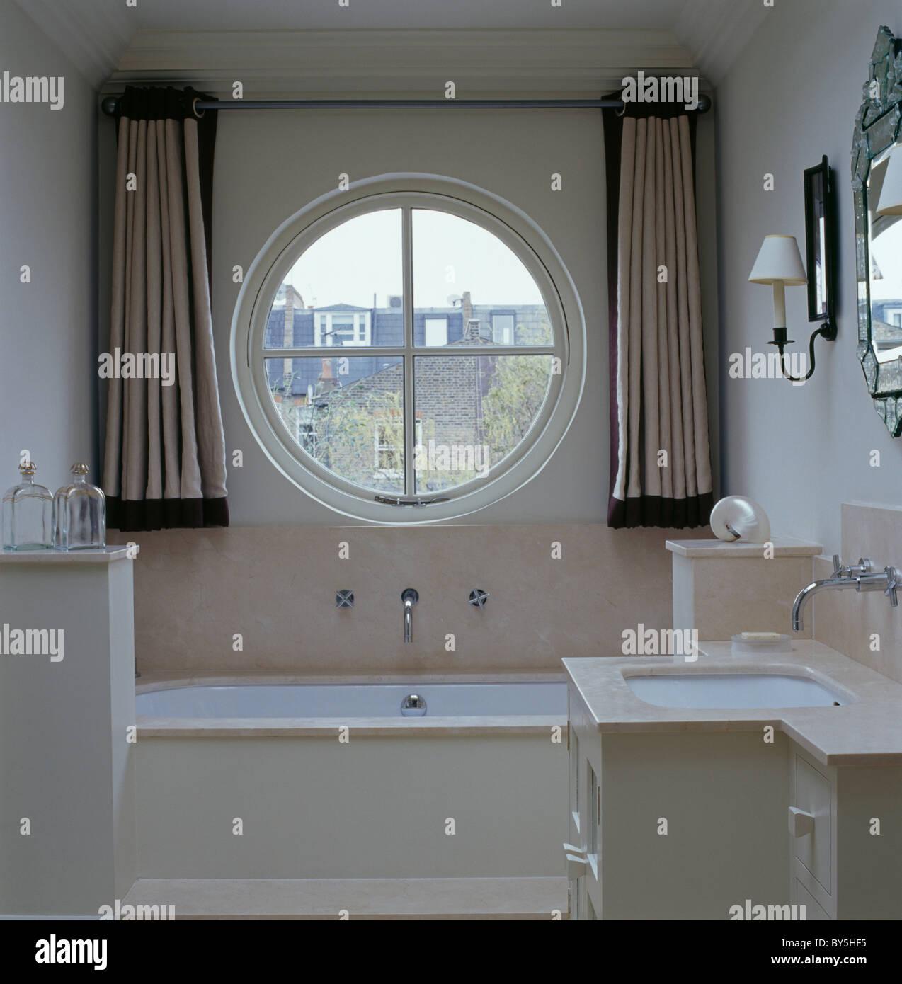 Beige Seidenvorhänge auf beiden Seiten des runden Fensters über Bad ...