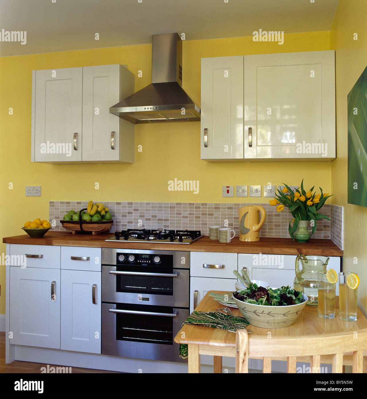 Elegant Edelstahl Abzugshaube über Dem Ofen In Modernb Gelbe Küche Mit Weißen  Montierten Einheiten Und Schränke