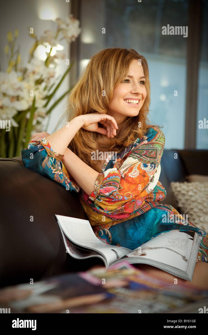 Junge Frau liest Magazin Stockbild