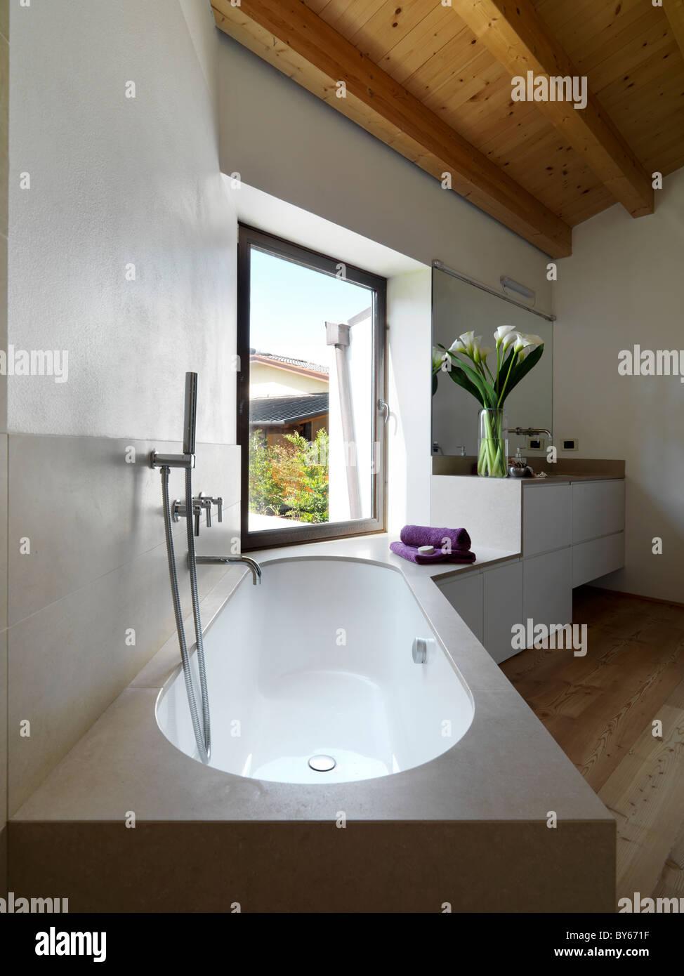 modernes Bad mit Badewanne und Waschbecken in Mansarde mit einem ...