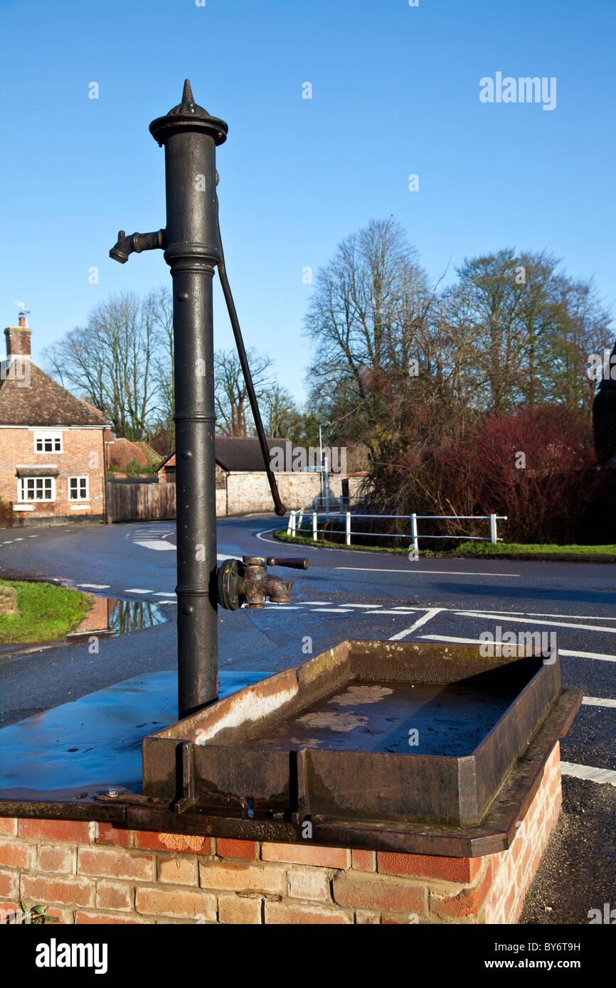 Eine alte gusseiserne Wasserpumpe an einem sonnigen Tag im Winter im Dorf Aldbourne, Wiltshire, England, UK Stockbild
