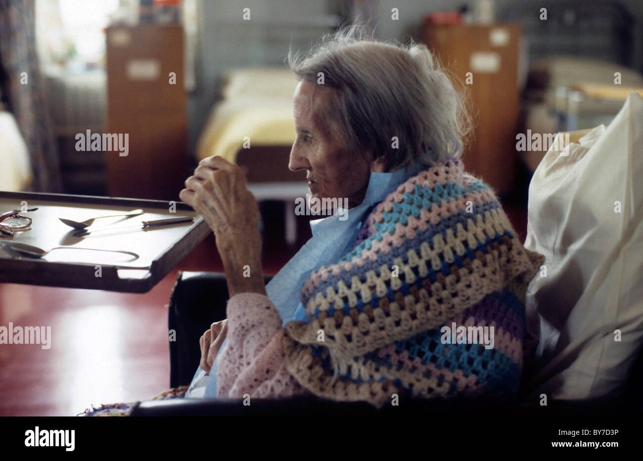Eine ältere Patientin trägt einen gehäkelten Schal von ihrem Nachttisch in einer Krankenstation in Stockbild
