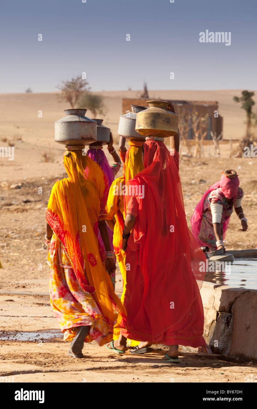Indien, Rajasthan, Frauen tragen von Wasser in der Nähe von Dorf-tank Stockbild