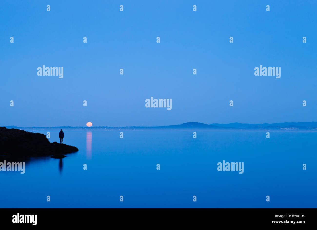 Eine Frau steht auf einer Küstenlinie beobachten die Einstellung Vollmond über Haro Strait und Vancouver Stockbild