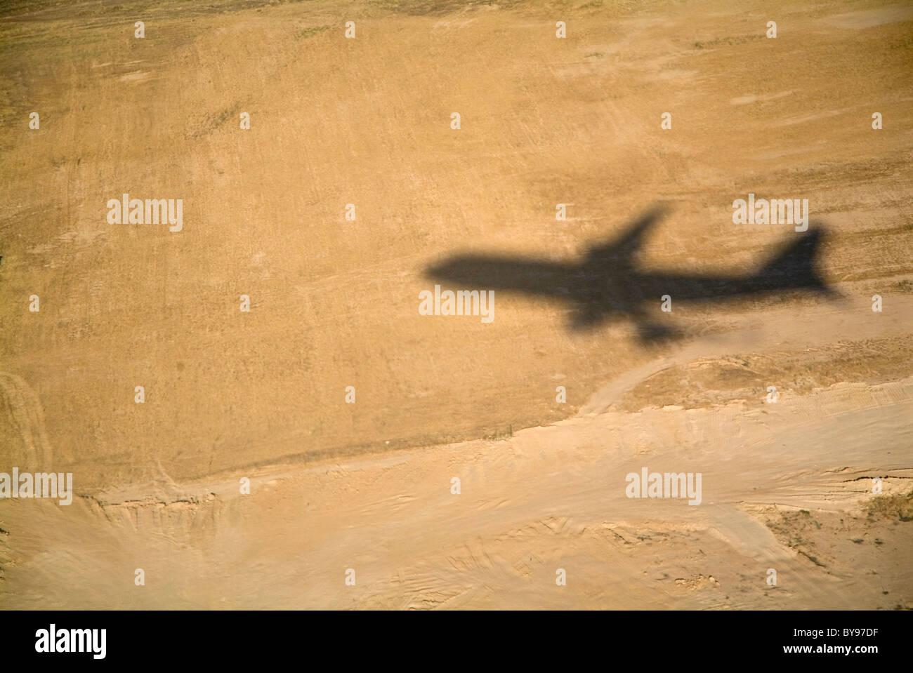 Schatten eines fliegenden Flugzeugs ausziehen Stockbild