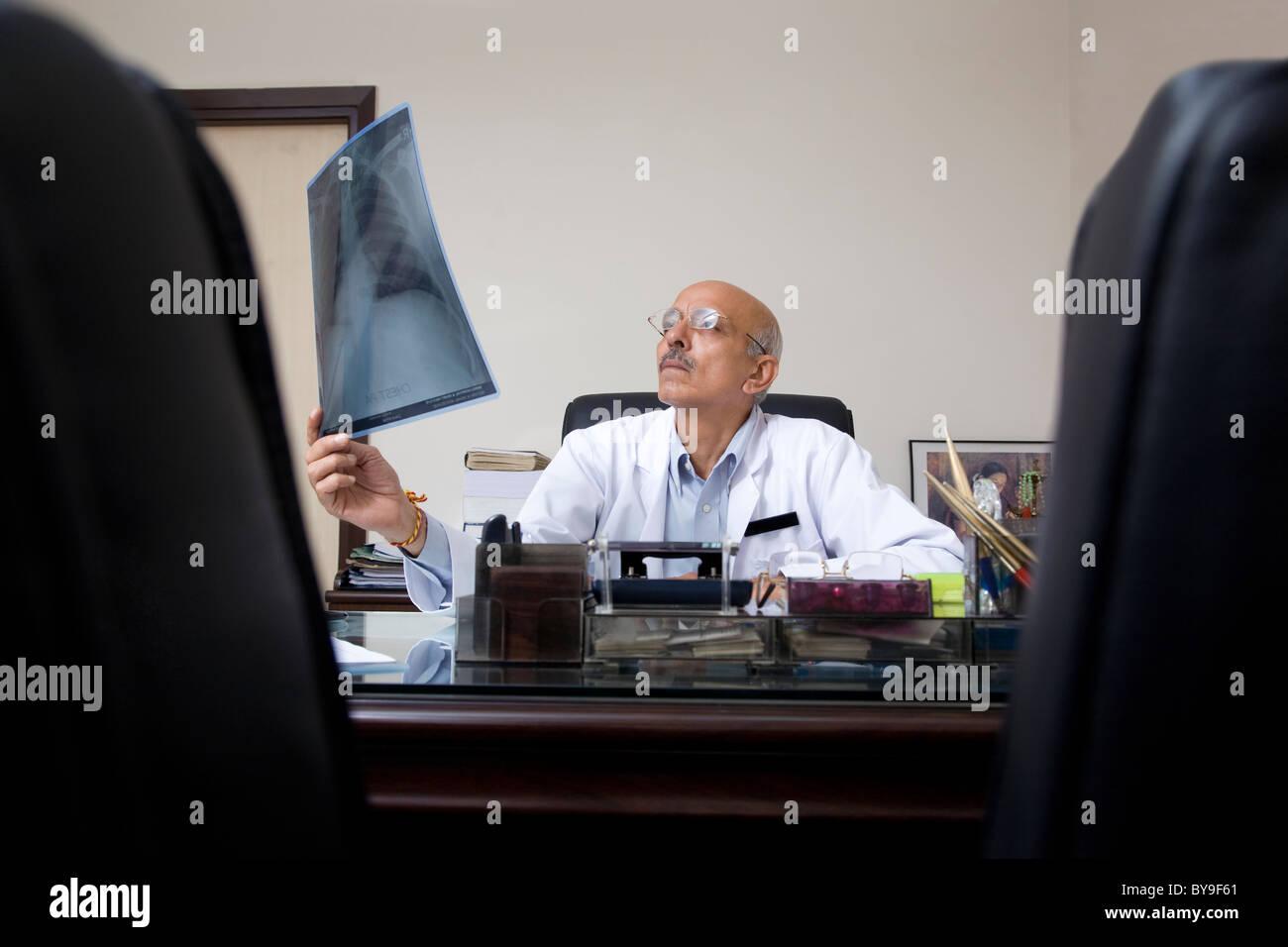 Arzt eine Röntgenaufnahme zu betrachten Stockbild