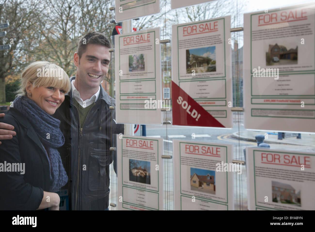 Paar auf der Suche in Immobilienmakler Fenster Stockbild