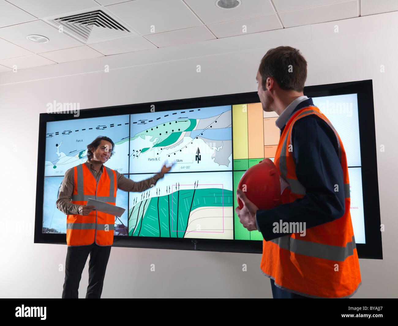 Öl-Arbeiter mit Geologie-Bildschirm Stockbild