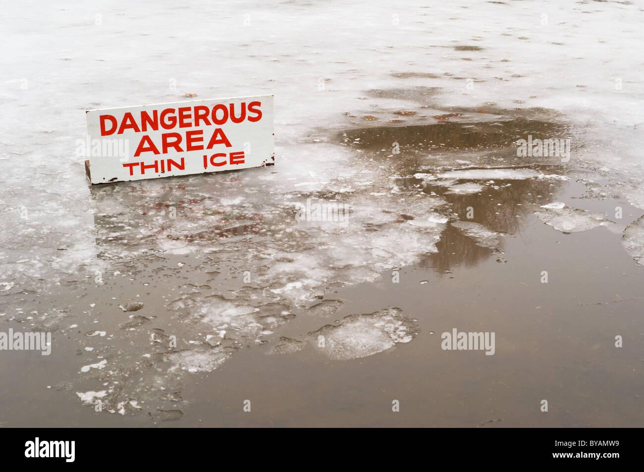 Ein Teich abgedeckt in einer dünnen Schicht aus Eis mit einigen open Water und ein Zeichen der Gefahr bedeutet. Stockbild