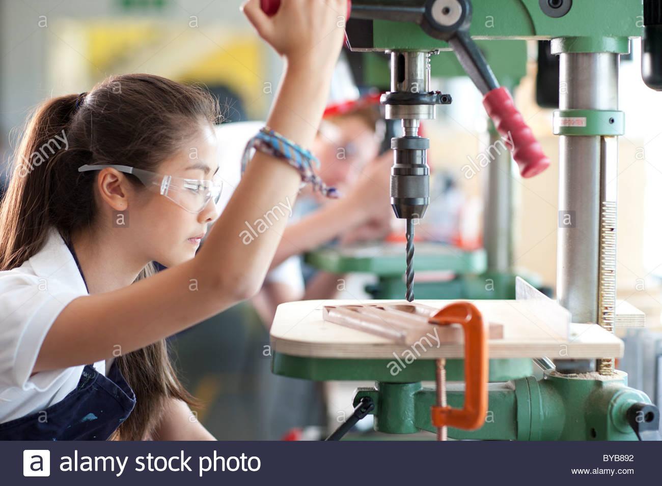 Ernsthaften Studenten mit Bohrer in der Berufsschule Stockbild