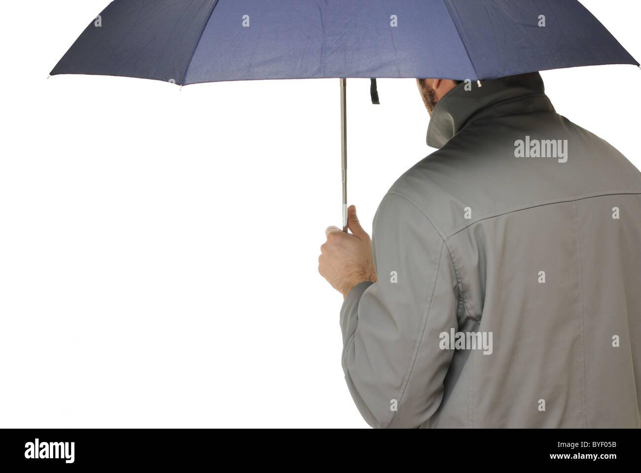 Mann mit Regenschirm und Regenmantel isoliert auf weiss. Stockbild