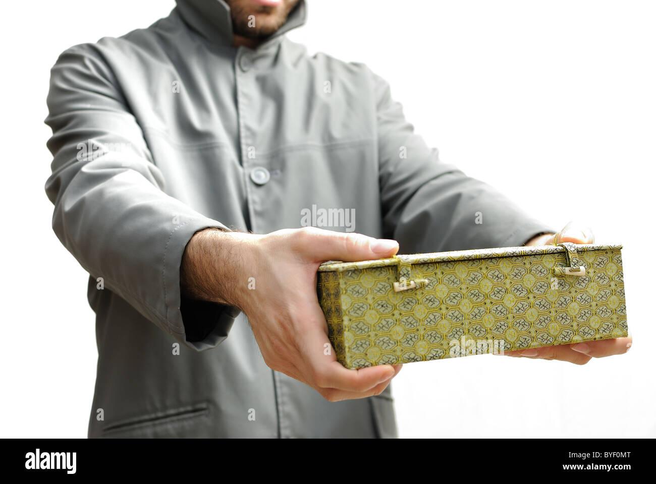 Mann im Regenmantel mit eine mysteriöse Kiste Stockbild