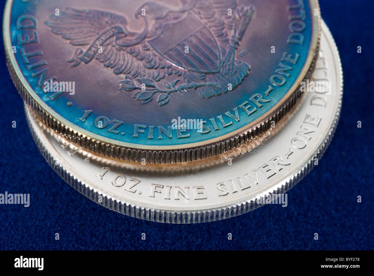 Eine angeschlagene Silbermünze neben einem nicht getrübt, eine für den Vergleich. Stockbild