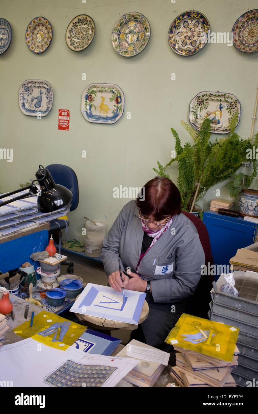 Frau malt keramische Fliesen mit Glasur in Viúva Lamego Fabrik in ...