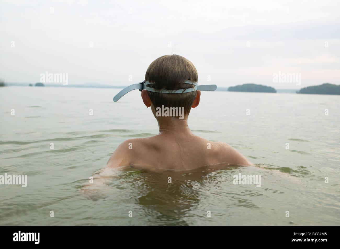 Junge, Schwimmen im See Stockbild