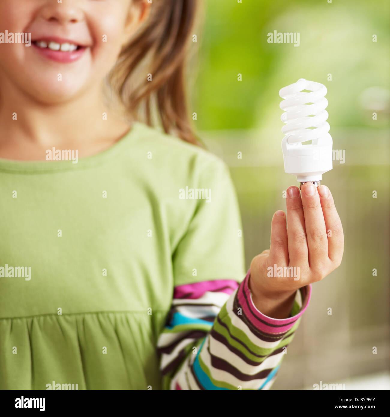 Mädchen hält die Glühbirne und lächelnd. Selektiven Fokus Stockbild