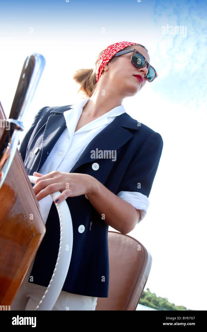 Junge Frau in Vintage-Kleidung Lenkung Boot Stockbild