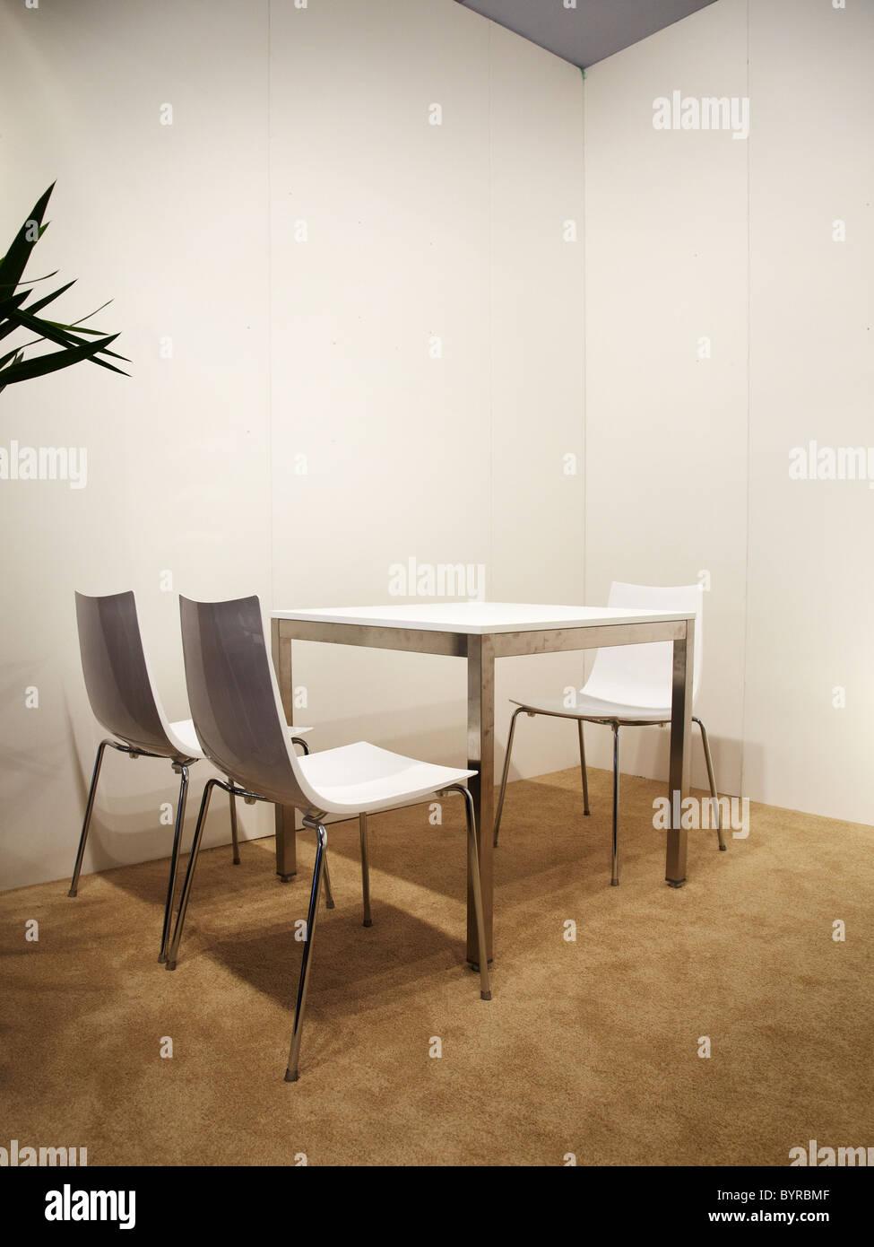 weiße Stühle und Tisch befindet sich im Innenraum mit weißen Wänden, Wartebereich, Rezeption, Stockbild