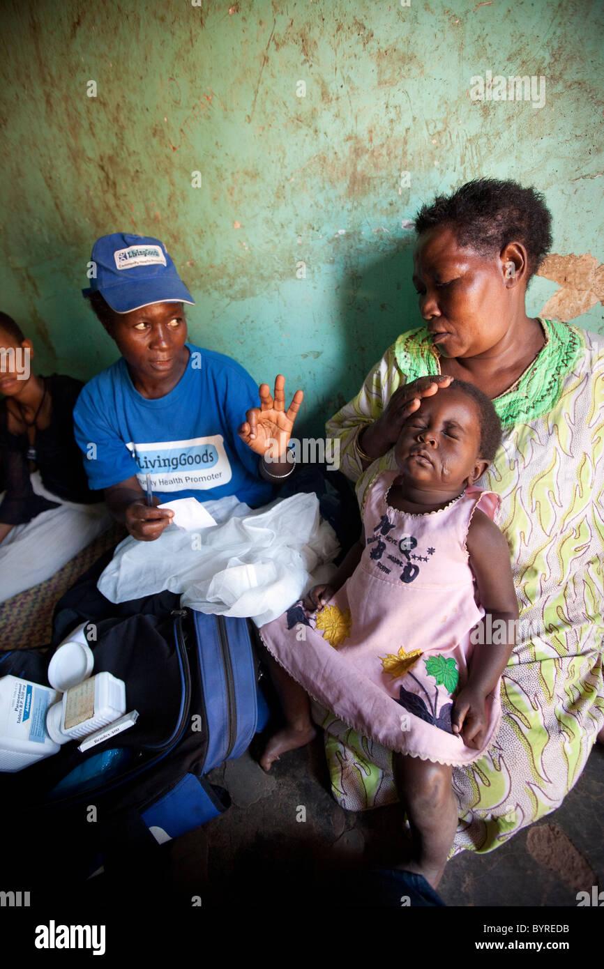Gesundheitswesen Heimarbeiter mit der NGO Leben Ware macht einen Besuch in eine Frau und ihre Kinder an Malaria Stockbild
