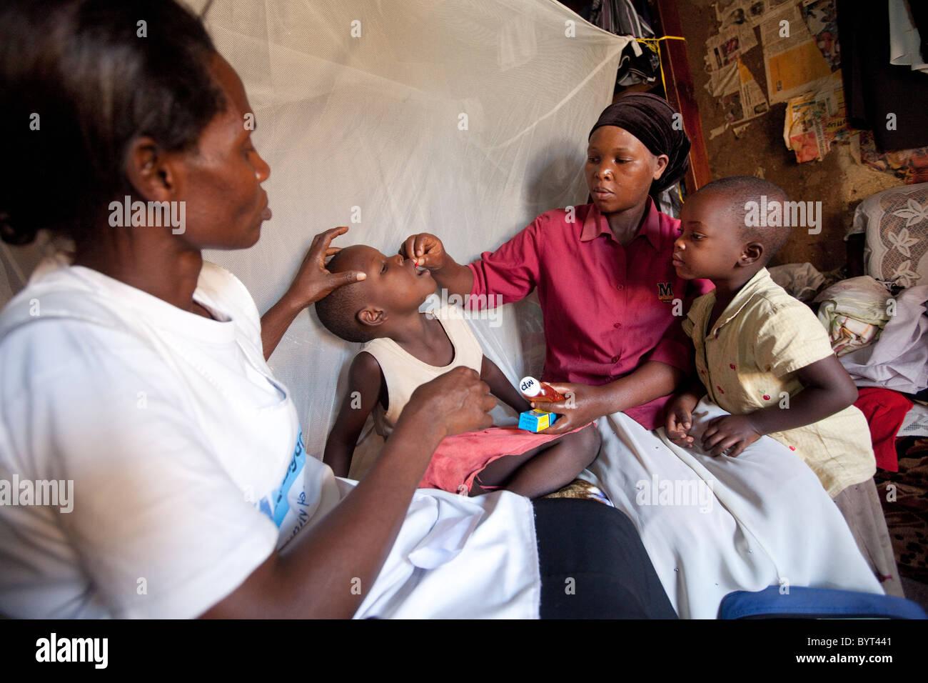 Ein Gemeindearbeiter Gesundheitswesen Outreach besucht eine HIV positive Familie in einem Slum in Kampala, Uganda, Stockbild