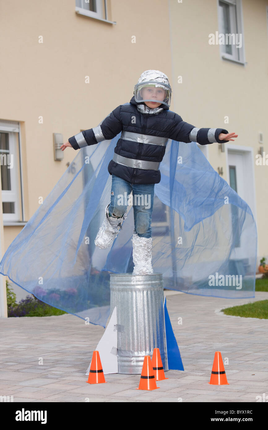 Junge gekleidet als Raumfahrer, versucht zu fliegen Stockbild