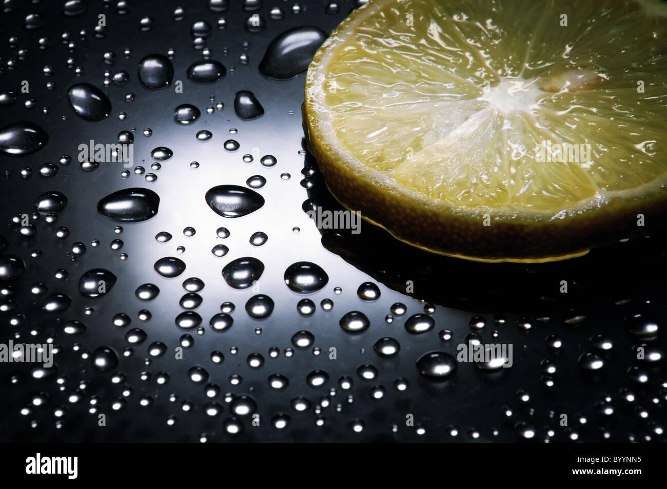 Zitronenscheibe, Wassertropfen, dramatische Beleuchtung, vertikal Stockbild