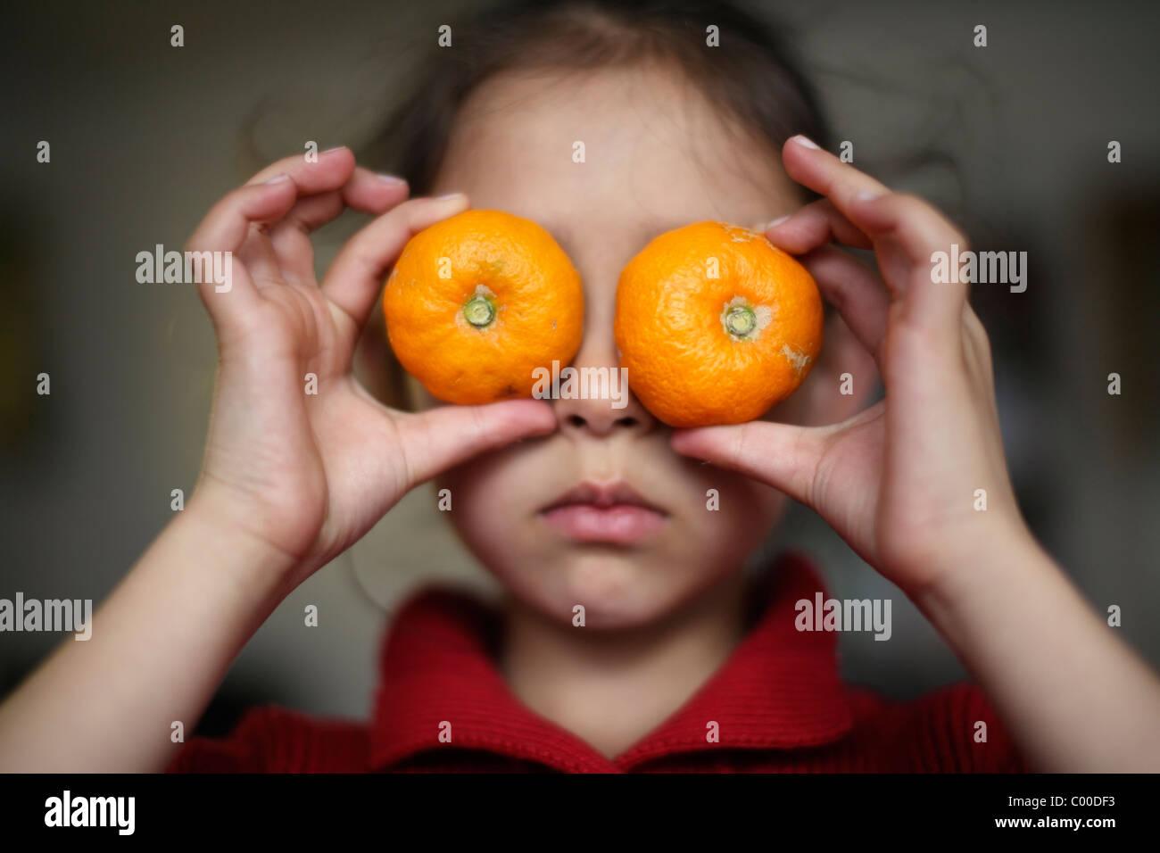 Mädchen hält Orangen über die Augen. Stockbild