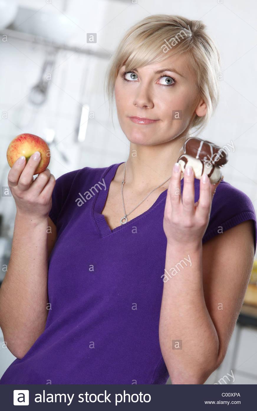 blonde Frau die Wahl zwischen Apple und donut Stockbild