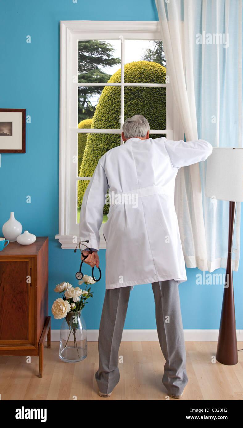 Männlichen Arzt im Haus späht aus Fenster auf riesigen Hecke. Stockbild