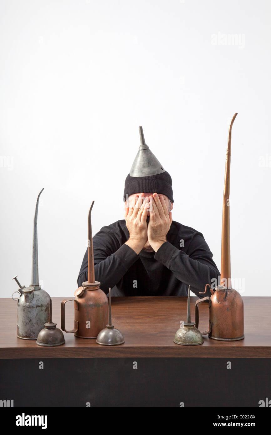 Mann mit Händen über Gesicht sitzt am Schreibtisch mit Ölkannen Stockbild