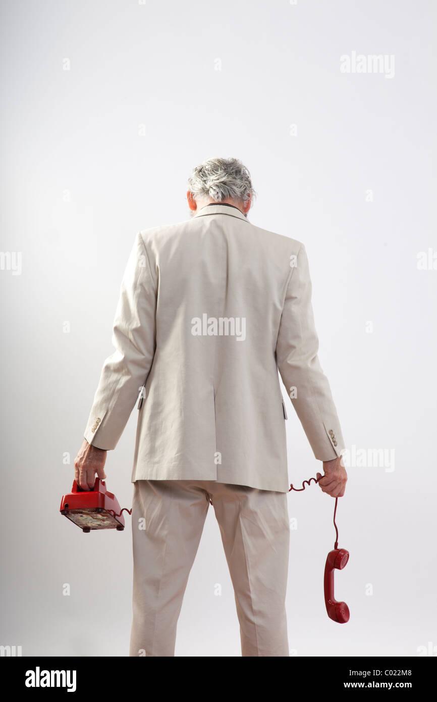 Mann an uns zurück halten rote Telefon baumelte in der Niederlage Stockbild