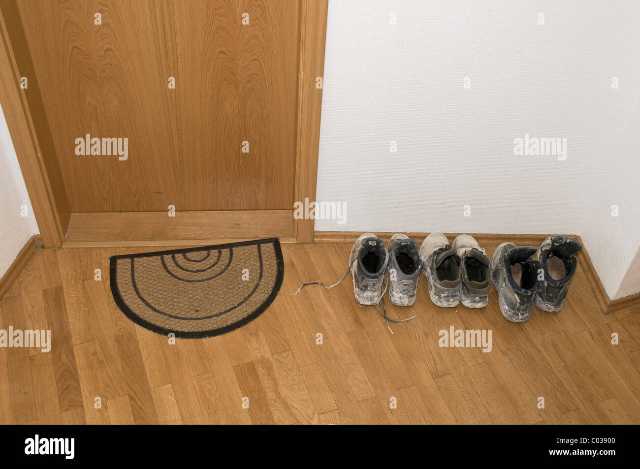 Schmutzige Schuhe im Flur neben der Eingangstür in einem Mehrfamilienhaus Stockbild