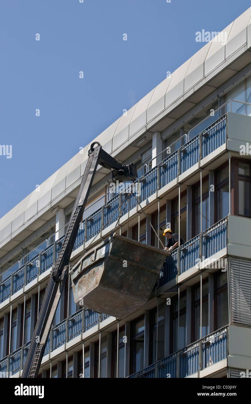 Konstruktion Abfallbehälter mit einem Kran auf das Dach eines Gebäudes, die saniert, ist aufgehoben Stockbild
