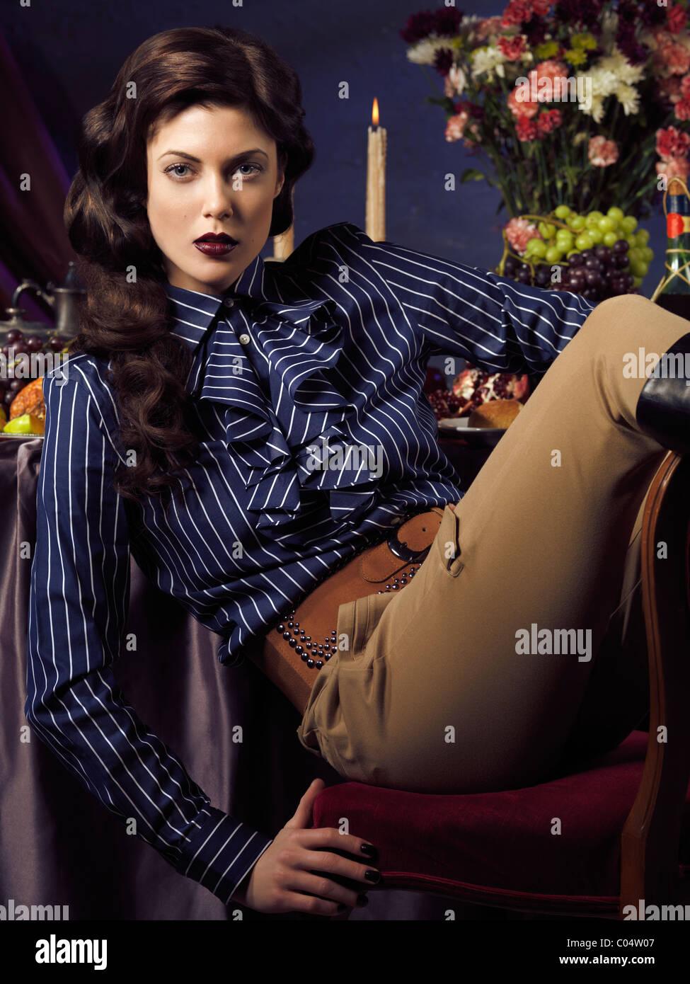 Künstlerische High-Fashion Foto einer schönen Frau sitzt an einem festlich gedeckten Tisch Stockbild