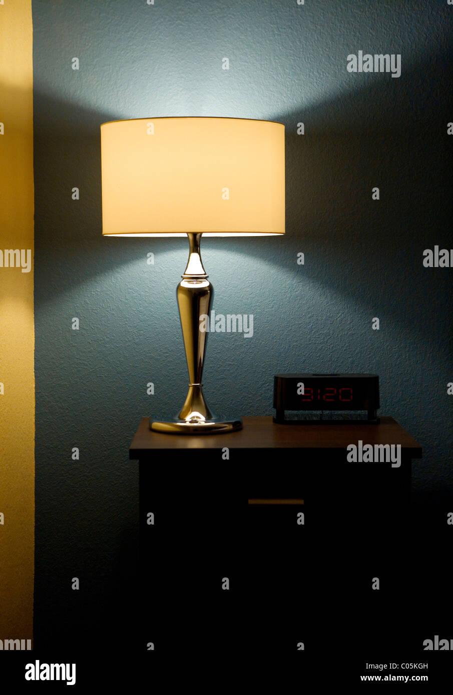 Lampe, Digitaluhr und Beistelltisch neben einem Bett. Stockbild