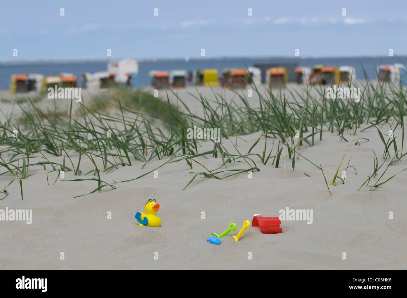 Urlaub, Kinderspielzeug auf einer Sanddüne vor überdachten Strand Korbsessel auf den Strand und das Meer, Stockbild