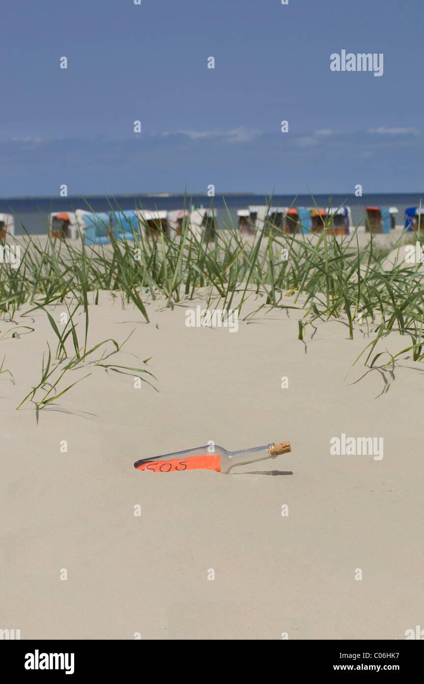 Flasche mit einer SOS-Nachricht auf einer Sanddüne vor überdachten Korbsessel Strand und die Nordsee, Stockbild
