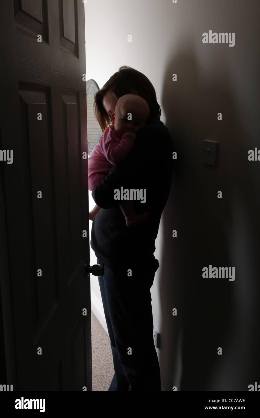 Silhouette der Mutter tröstet ein Baby, Kopf nach unten an der Wand leicht geöffneter Tür gelehnt. Stockfoto