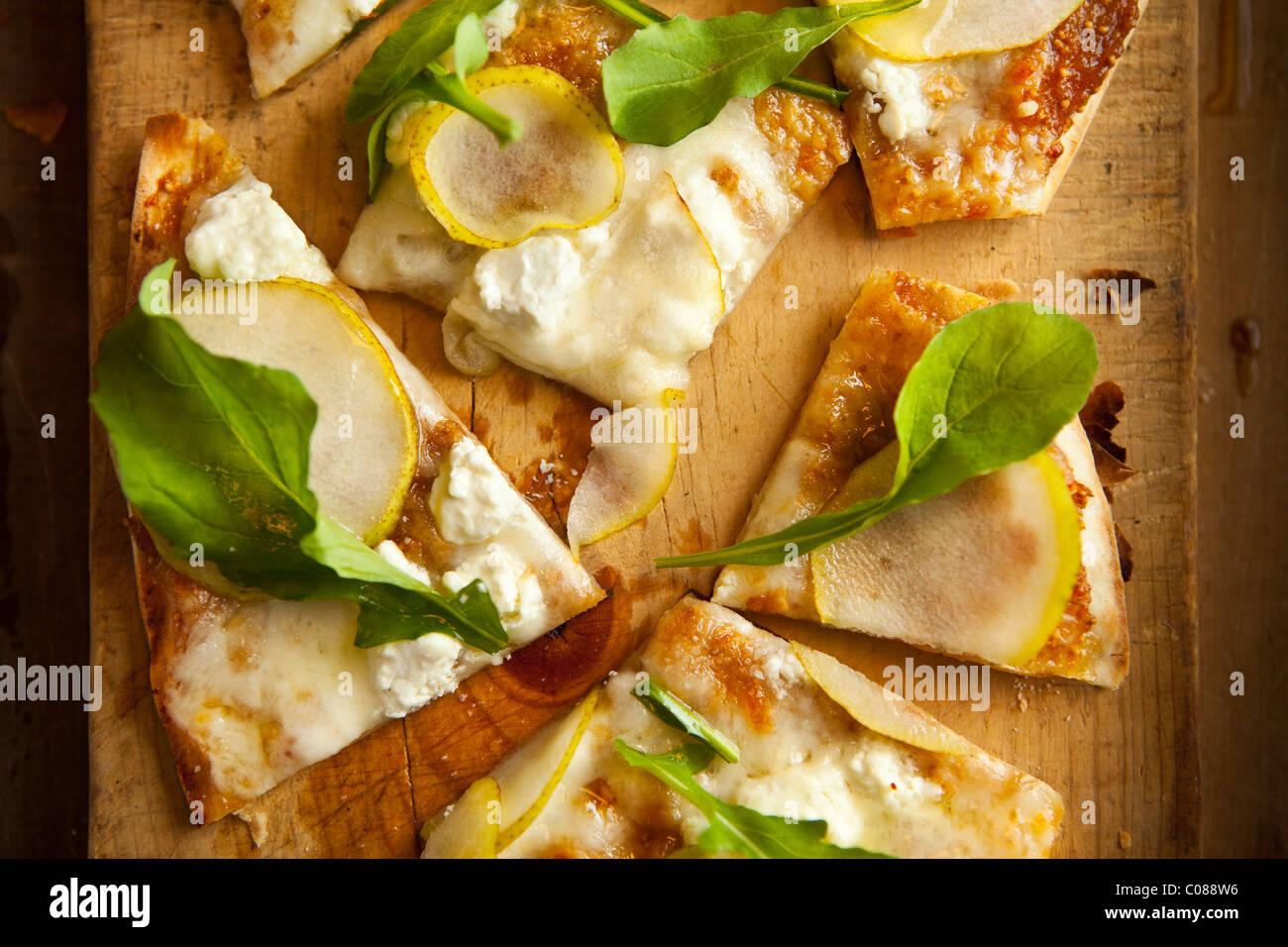 Dünne und knusprige Kruste Pizza mit Mozzarella, Ziegenkäse, Feigen zu verbreiten, Birne und Rucola von Stockbild